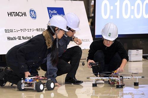 ◇廃炉という難題に挑む/競技フィールドで「ドローン」をセッティングする熊本高専チーム。コンクリートの厚い壁で電波が届きにくいことを考慮し、無線通信の中継器を搭載した小型車を組み合わせることで、ケーブルを使わない制御を目指した。背後には持ち時間を表示する時計。放射線量の多い廃炉作業を想定することから、時間制限も重要な課題となった