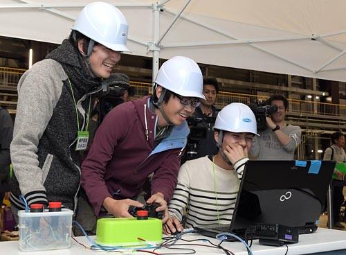◇ロボットの挙動に歓喜/遠隔操作でロボットが順調に動き出し、笑みがこぼれる東京高専チーム。2階に置かれた物体を調べる課題に挑戦し、直接階段を上るのではなく、階段の脇からはしご車のような機構を展開した。調査の結果「スパナ」の発見に成功。競技全体で唯一の課題クリアとなった