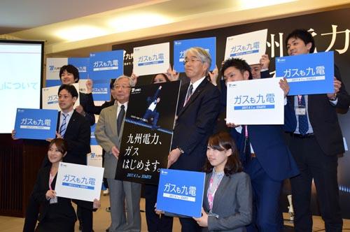 九州電力は20日、4月から福岡・北九州エリアで販売を始める家庭用など小口の都市ガス料金プランを発表した。電気とガスの「セット契約」のみの提供で、電気契約容量やガス使用量が多いほど「セット割引」を大きくする仕組み。写真は、都市ガス料金メニューの発表でポスターを掲げPRする九州電力の瓜生道明社長(中央左)と渡辺義朗取締役・常務執行役(同右=20日、福岡市内)