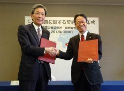 売買契約書に調印、握手を交わす北海道電力の真弓社長(右)と関西電力の岩根社長
