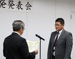 尾崎理事長(左)から最優秀賞の茨城事業本部の担当者に賞状が授与された