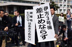仮処分申し立ての棄却を伝える原告側代理人(30日、広島市の広島地裁前)