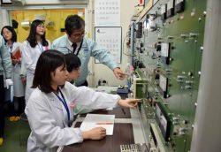 教員の指導を受けながら学生が原子炉制御盤の操作を行った
