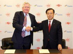 合弁会社設立式で握手する原電の村松社長(右)とエクセロンのクレーンCEO
