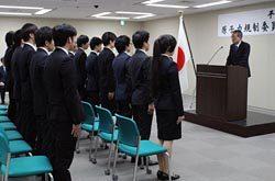 新規採用職員を前に訓示する田中委員長(右)