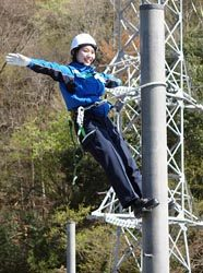 頂上で昇柱完了を宣言する新入社員