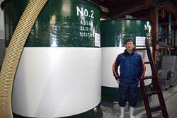 発酵用タンクの前に立つ三宅代表取締役