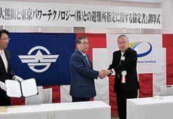 協定に署名し握手を交わす原社長(右)と渡辺町長