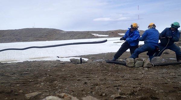 関電工から極地研究所の第57次南極地域観測隊越冬隊に派遣されていた岡本龍也さんと、第58次隊夏隊に派遣されていた内山宣昭さんがこのほど、帰国した。写真は、現在南極に滞在している第58次隊越冬隊の齋藤健二さんと3人で昭和基地のケーブル引き替え作業を行う様子