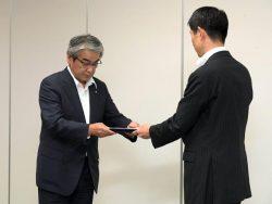 市村管理官(右)から原子炉設置変更許可書を受け取る森中常務執行役員(24日、東京・六本木)