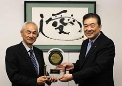 ジェイ・ディー・パワーの鈴木社長(左)からトロフィーを受け取るエネコムの熊谷社長