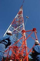 39号鉄塔の組み立て作業。タワークレーンで部材を慎重に吊り上げ、塔上作業者との連携プレーで据え付けた