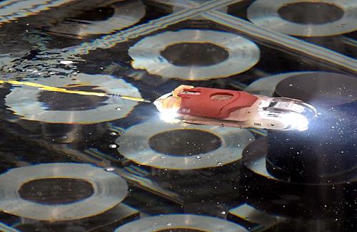 今回開発されたのは直径約13センチメートル、長さ約30センチメートルの小型水中遊泳ロボット。有線ケーブルで電源供給や通信を行い、遠隔で操作する。後方4つ、上方1つのスクリューで推進する。報道公開は海上・港湾・航空技術研究所の港湾空港技術研究所(神奈川県横須賀市)で行われた。
