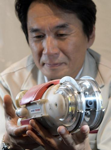 ロボットは直径約13センチメートル、長さ約30センチメートル、重さ約2キロで愛称は「ミニマンボウ」。東芝では、これまでも水中を泳ぐロボットを用いて原子炉内部の点検を実施していたが、3号機では格納容器内部にアクセスするための貫通部分が直径約14センチメートルと小さいため、従来型のロボットを小型化するとともに、耐放射線性を高めた。