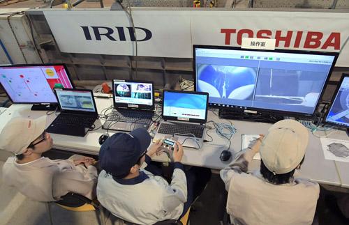 ロボットから送信される映像を見ながら操作する職員。圧力容器底部の構造物の損傷状況を確認し、さらに下へと潜水できるルートがあればペデスタル底部の状況も調べる。