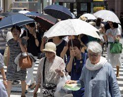 東京・銀座ではタオルで汗を拭う人や日傘を差して歩く人の姿が目立った