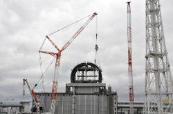 原子炉建屋に屋根カバーの2個目の部材が取り付けられ、かまぼこ状の形が一部できあがった(2日、福島第一原子力発電所)