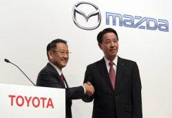 会見で握手する豊田・トヨタ自動車社長(左)と小飼・マツダ社長兼CEO(4日、東京・日本橋)