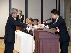 経産省の大串政務官(右)から表彰状が授与された(1日、東京・霞が関)