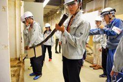 事故当時の復旧作業で敷設されたケーブルを持ち上げ重さを確認する生徒ら