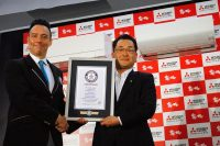 新製品を前にギネス認定で握手を交わす鈴木所長(右)とパターソン氏