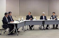 更田新委員長(中央)の下開催された臨時委員会。田中委員(左から2人目)を委員長代理に指名した(22日、東京・六本木)