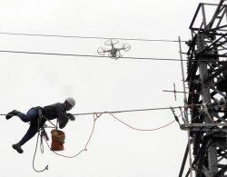 電線に乗り出し補修する作業者とライブ伝送訓練で飛行するドローン