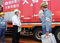 大容量ポンプについて関電社員から説明を受ける中塚町長(中央)