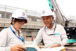 現場で工事担当者と打ち合わせする大和ハウス工業の小部さん(左)