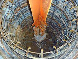 深礎基礎坑に設置した架台とその上に据え付けた鉄塔基礎材(中央)。周囲を配筋し一度にコンクリートを打設する