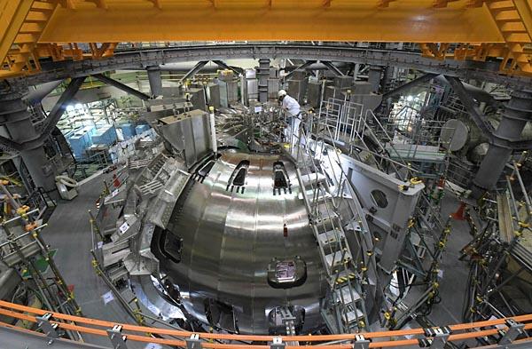 磁場コイルの据え付けが進むJT-60SA。中心に見えるのがプラズマを閉じ込めるドーナツ型の真空容器。左側まで磁場コイルが回し込まれている