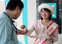 食堂利用者に一口サイズの塩むすびを手渡す「ミス・クリーンライスあおもり」の立崎さん