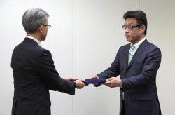 規制委の小野安全規制管理官(左)から原子炉設置変更許可を受け取る東電HDの牧野取締役(27日、東京・六本木)