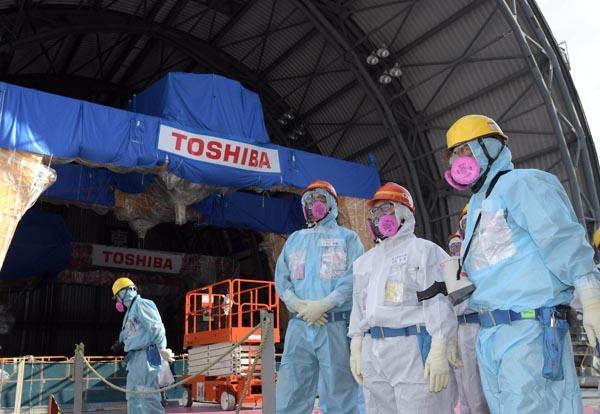 世耕弘成経済産業相は18日、東京電力福島第一原子力発電所を視察した。写真は、東京電力ホールディングス(HD)の小早川智明社長(右から3人目)らの案内を受け、3号機原子炉建屋最上部で視察する世耕経産相(同2人目)