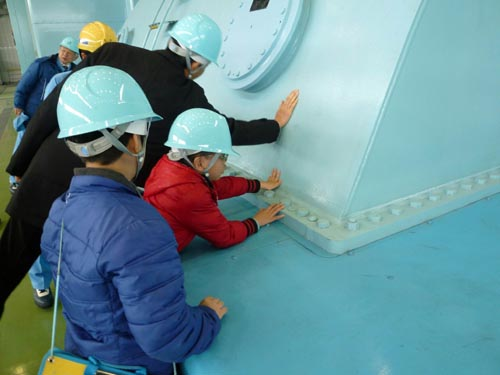 蒸気タービンが発する振動や熱を、手で触って実感する児童(写真提供:東北電力)