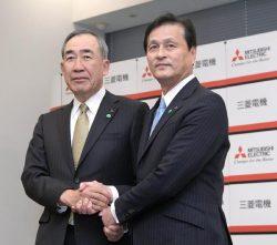 会見終了後握手する杉山次期社長(右)と柵山社長(21日、東京・丸の内)