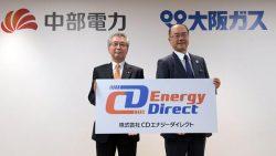 会見で新会社名が書かれたボードを手にする中部電力の勝野社長(左)と大阪ガスの本荘社長(27日、東京・丸の内)