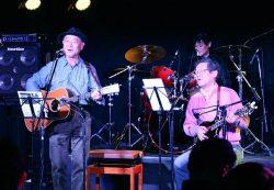 大盛況となった初ライブでギターと歌声を披露する山元社長(右)
