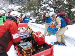 雪上運搬車から機材を降ろす中国電力の参加者(右)