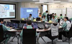 事務本館内の緊急時対策室で訓練を指揮する工藤社長(右)