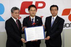 協定書を手にする四国電力の佐伯社長(右)、JR四国の半井社長(左)、日本郵便の丸山支社長