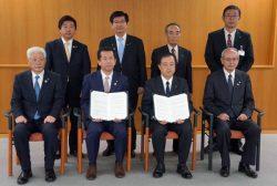 協定を締結した関係自治体の首長ら。前列右から2人めが村松社長(3月29日、東海村役場)