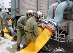 送水ポンプ車にホースを接続する作業員