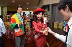 「ミスりんごあおもり」の小野さん(中央)らが2種類の青森県産リンゴを配った
