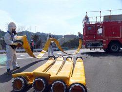 可搬型ホースを運搬する訓練参加者(12日)