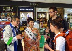 空港利用者に自社ブランドの日本酒をPRする末廣酒造の新城社長(左)