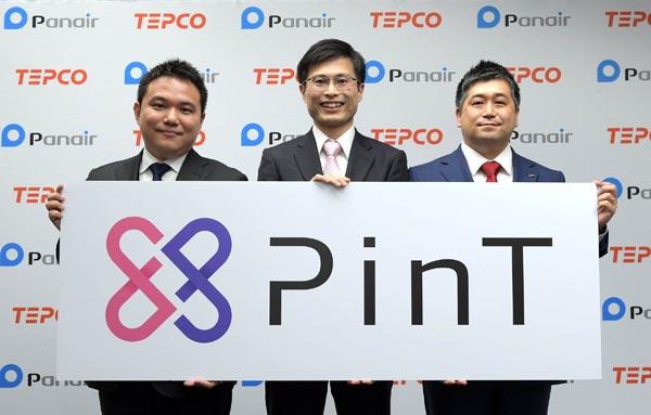 新会社のロゴを掲げる(右から)東電EPの田村常務取締役、新会社の田中社長、パネイルの名越社長(24日、東京・内幸町)
