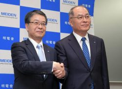 会見で握手する三井田次期社長(左)と浜崎社長(14日、東京・大崎)