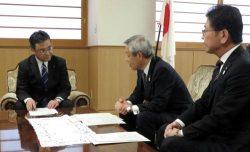 青森県議会の熊谷議長(左)に工程変更を説明する増子副社長(中央=24日、青森県庁)