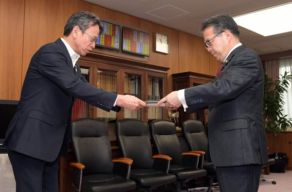 世耕経産相(右)に届出書を提出する岩根社長(28日、東京・霞が関)